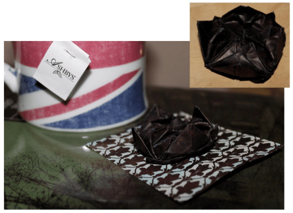 """Make a Sherlock Black Lotus pin by using dark paper with and origami """"lotus blossom"""" pattern."""