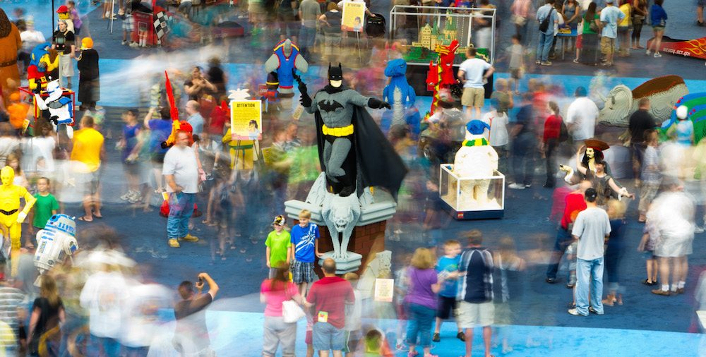 Image of the LEGO Model Museum. Some motion blur highlights the activity and a life sized Batman is featured at the center of the image