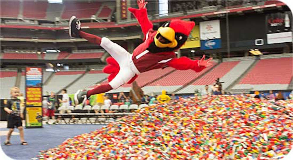 Arizona Cardinals mascot Big Red diving into a huge pile of LEGO bricks