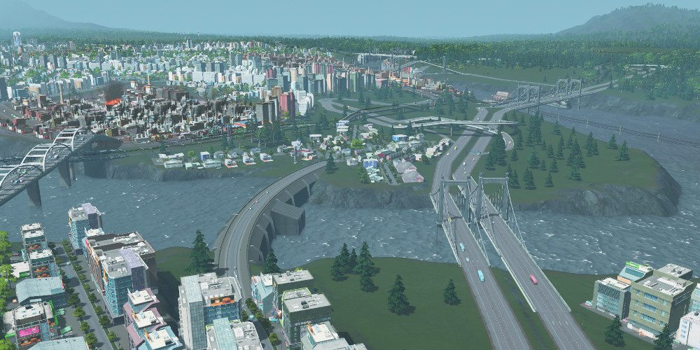 A dam with cars on its top road blocks a river, showing the difference in heights from up to downstream.