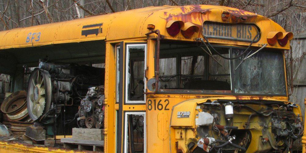 An abandoned school bus is on a scrap yard.