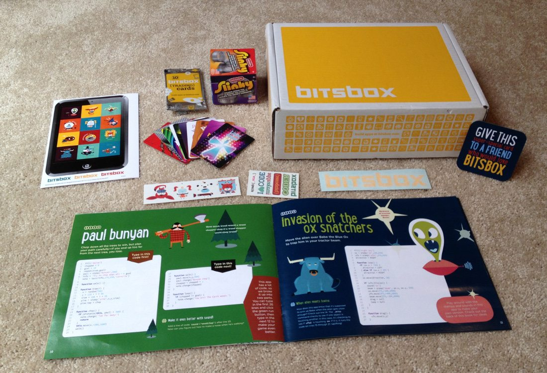 Shows the contents of a Bitsbox including the app book, stickers, trading cards, and mystery toy, a Slinky
