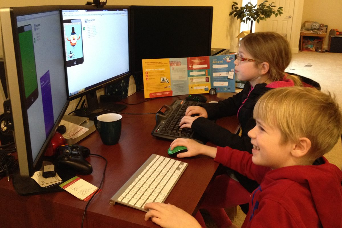 A girl and a boy sit side by side, in front of keyboards, looking at screens where they are writing programs in Bitsbox.