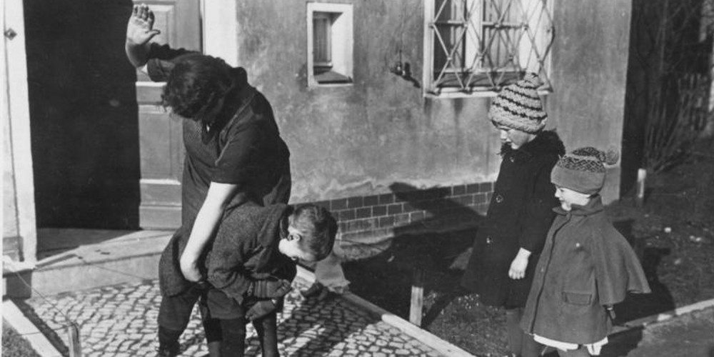A woman spanks a child while two peers look at what is happening.
