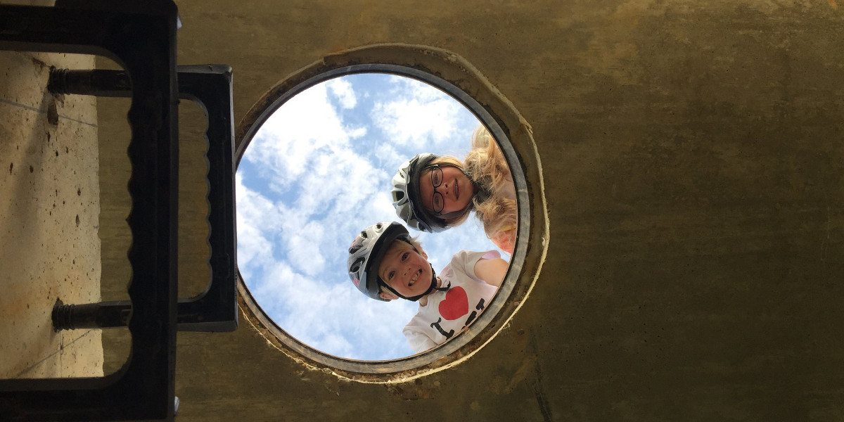 A boy and girl wearing bicycle helmets look down through a manhole cover. The shot is taken from inside the sewer, looking up at the children framed behind the manhole and the sky.