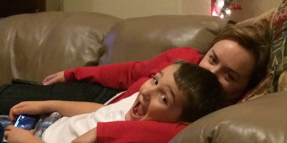 Kid excitedly playing a game on his iPhone while laying on the couch with mom.