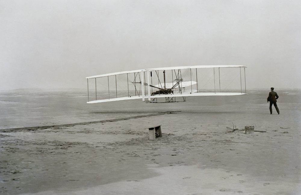 First flight of the Wright Flyer I, December 17, 1903, Orville piloting, Wilbur running at wingtip. Photo: Public Domain