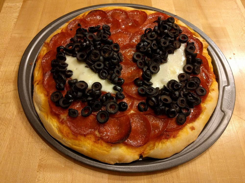 A pepperoni pizza made to look like Deadpool's mask.