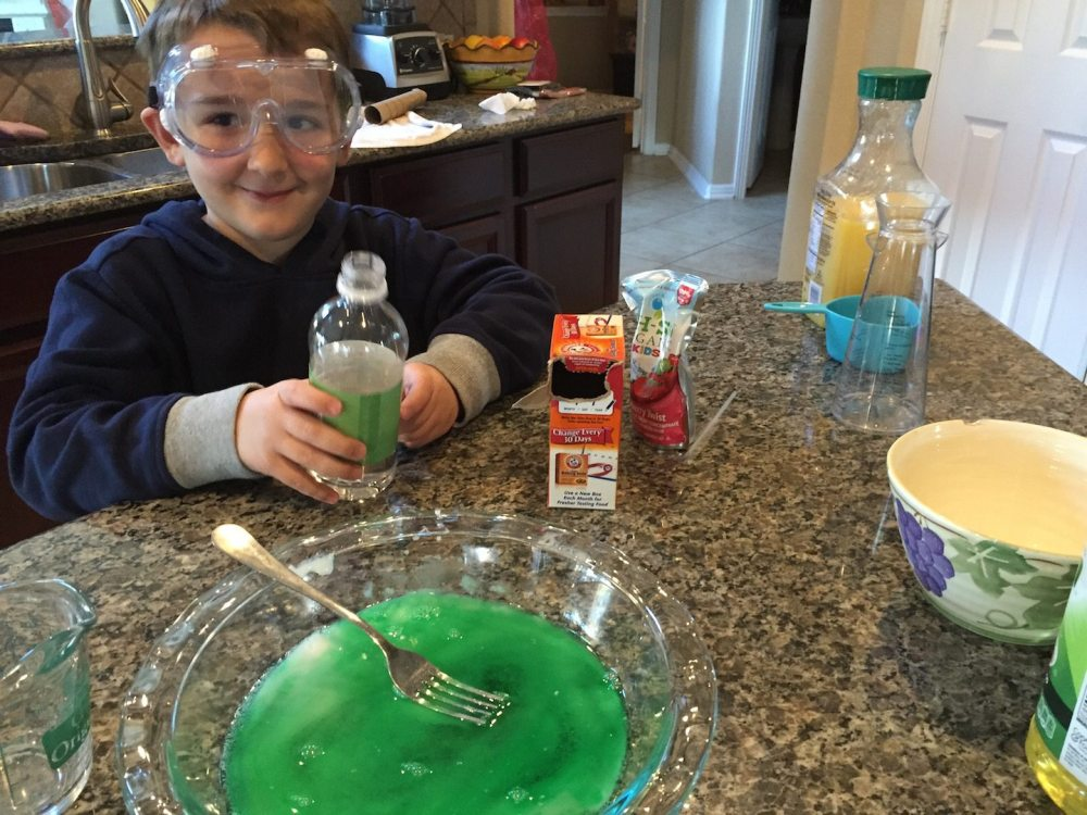 Kid holds a bottle of vinegar next to a large flask of green liquid after the formal part of the science fair project is over.