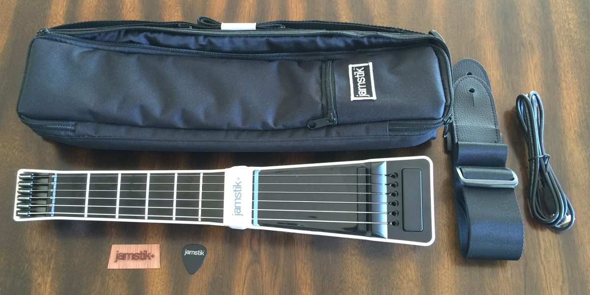 The contents of a jamstik+ delivery including the jamstik+, carrying case, strap, micro USB cable, wooden face plate, and pick.