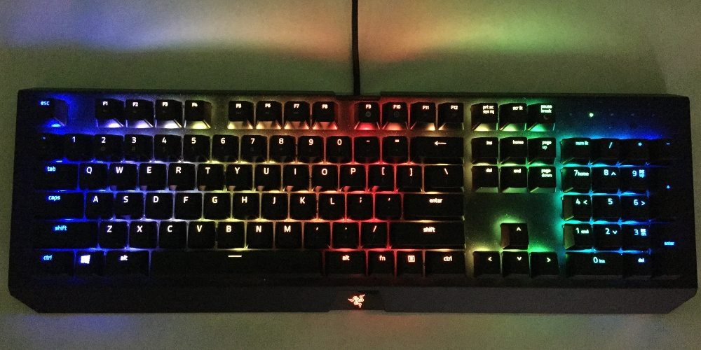 A close-up of the Razer BlackWidow X Chroma, in wave setting, having rainbow waves of light across its keys.