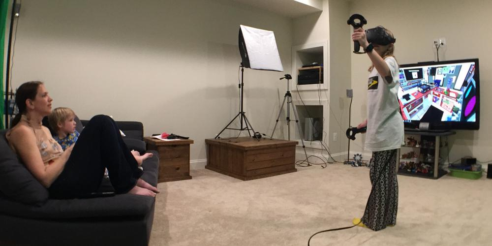 Family sitting on a couch watching a girl with a VR headset playing the HTC Vive, with Job Simulator on the TV behind her.