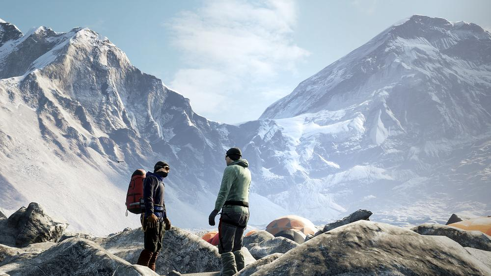 Two climbers in gear stand in front of tents at Everest base camp, the mountain looming behind them.