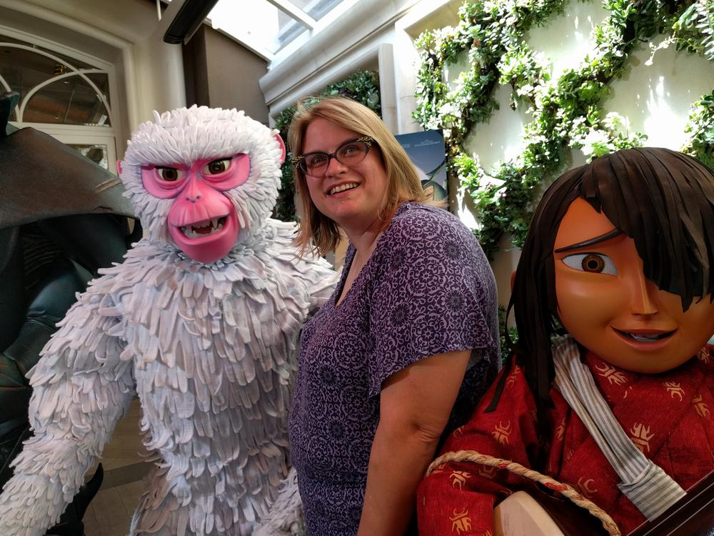 Marziah Karch posing with characters from Kubo and the Two Strings.