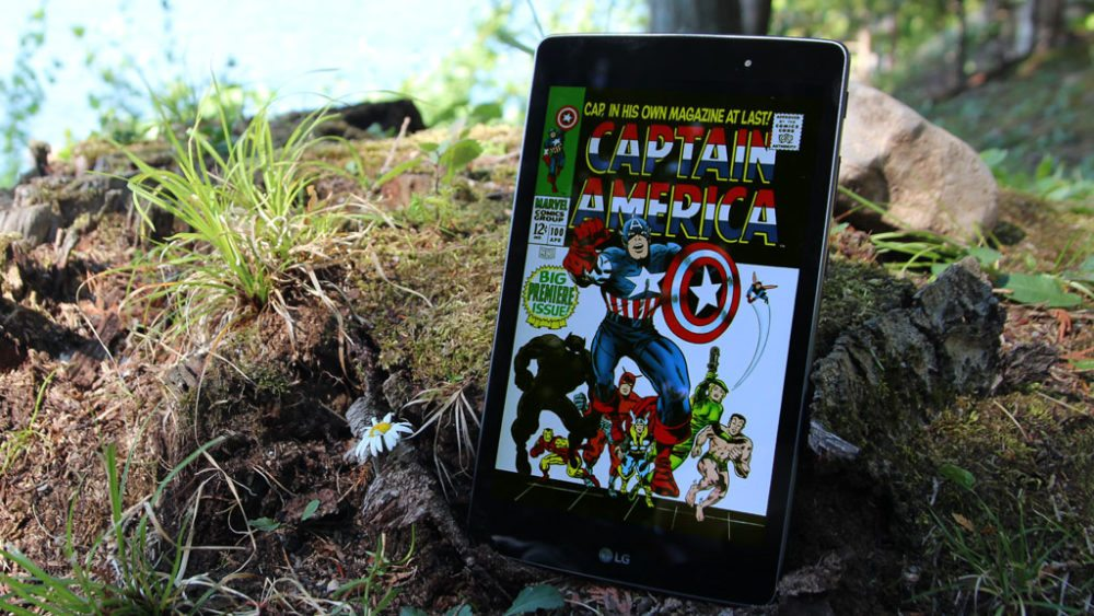 Tablet with Captain America comic cover leaning on a tree stump