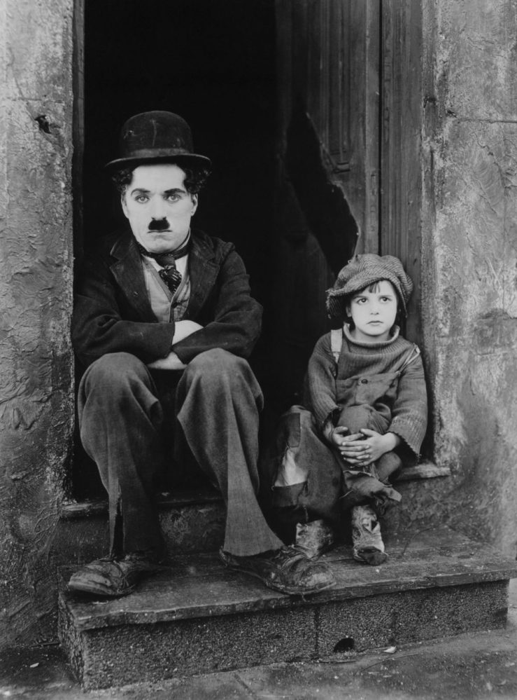 Publicity photo from Charlie Chaplin's 1921 movie 'The Kid.' Pictured are Charlie Chaplin and Jackie Coogan. Image is public domain.