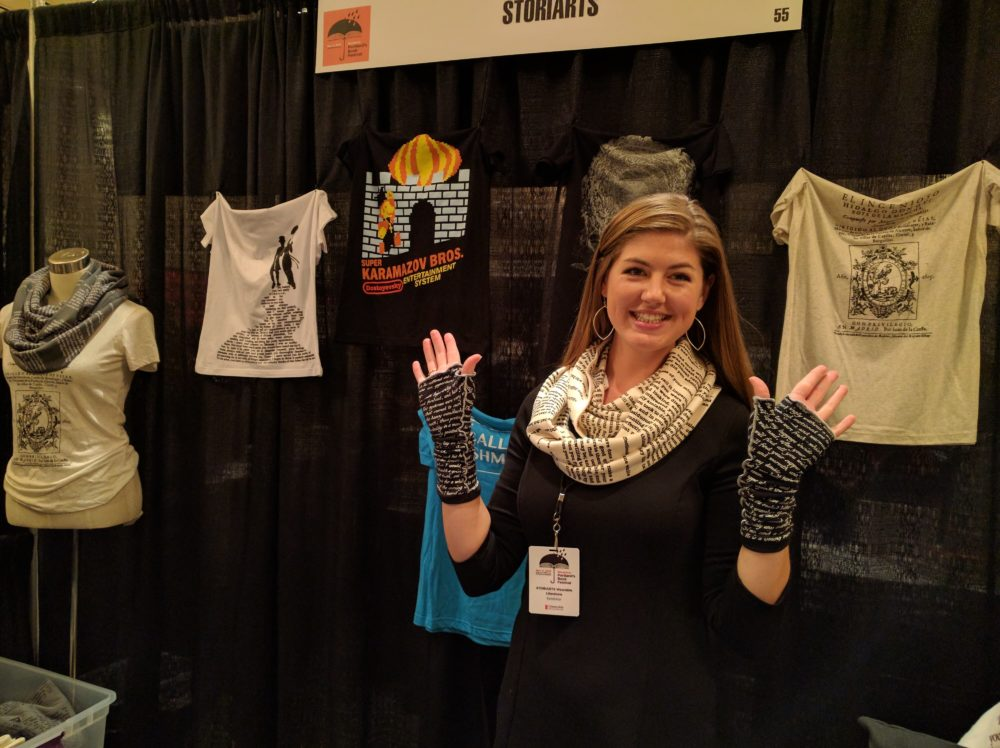 A woman demonstrates her literary scarves and hand warmers