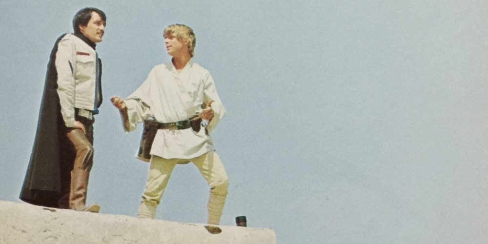 Luke Skywalker stands on the edge of a terrace, talking with his friend Biggs.