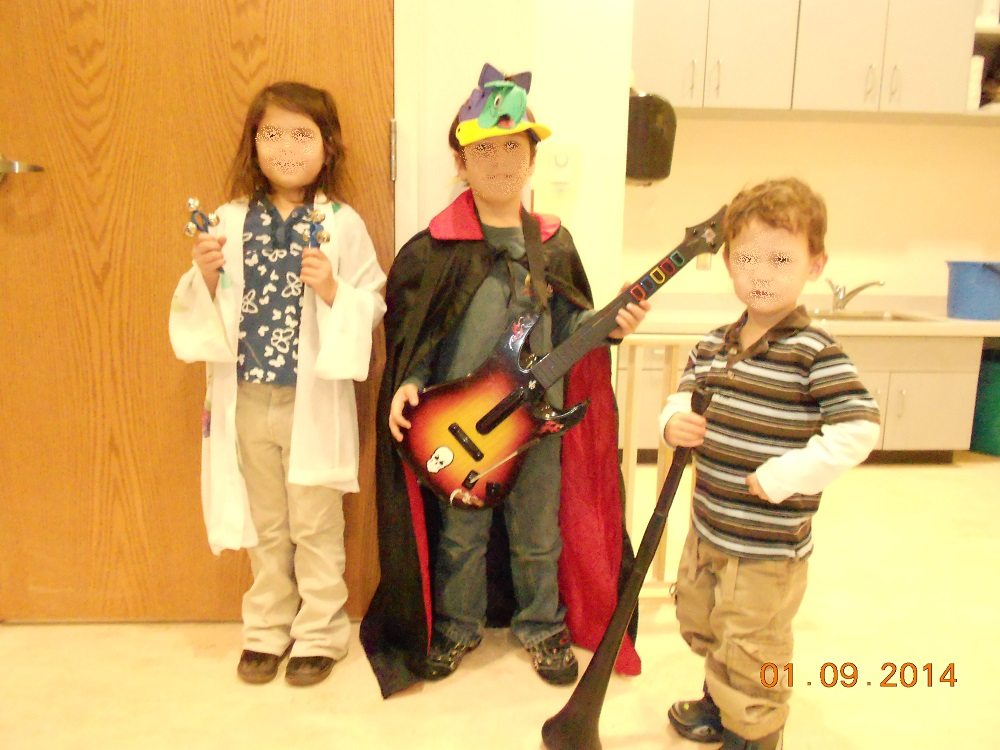 three children in random bits of costume hold toy instruments