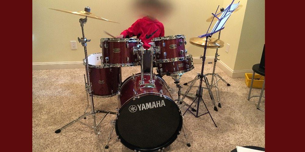 image of kid playing Yamaha Rydeen drum kit