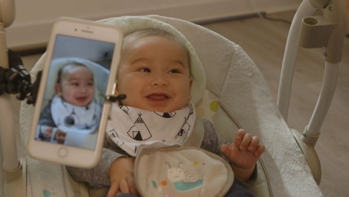 An infant smiles while an iPhone snaps photos of him