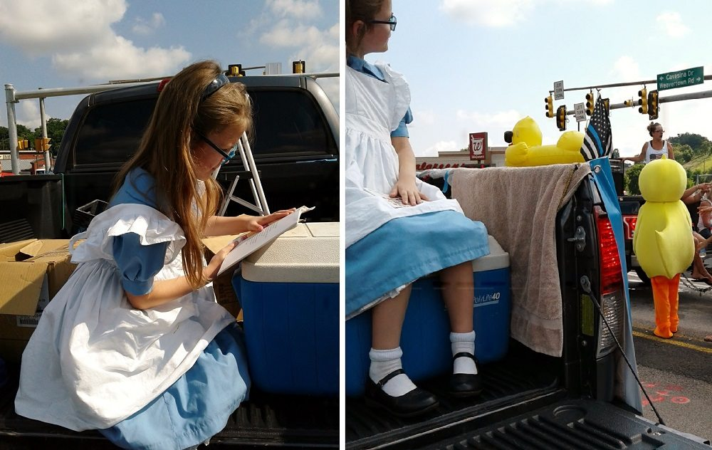 Girl in Alice in Wonderland costume reads in the back of a truck and watches another marcher in a duck costume - first cosplay