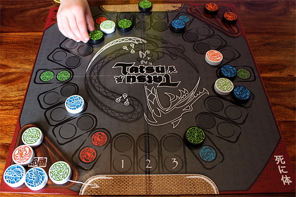 A game of Tatsu in play, Team Black has a green vine dragon on their mat ready to launch, and on the right, Team White's vine dragon holds one of Team Black's water dragons, Image: Sophie Brown