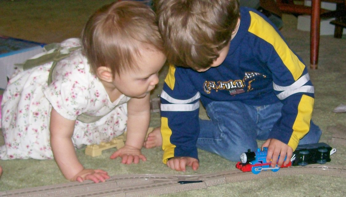 3yo plays with a Thomas the Tank Engine while his 1yo sister looks on closely