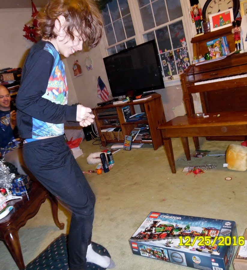 9yo boy in pajamas jumping up and down with his new Lego Holiday Train box in front of him