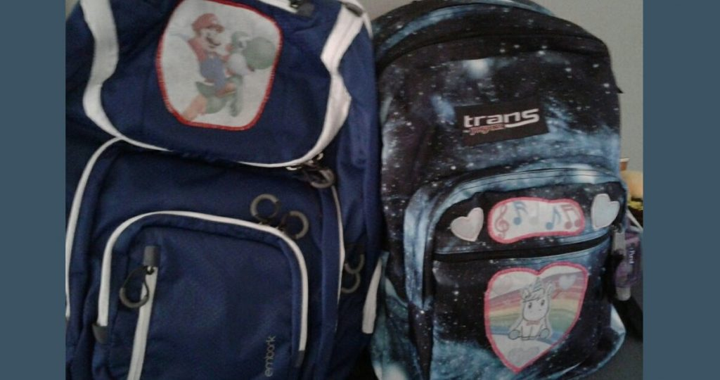 Two backpacks, one has a patch of Mario riding Yoshi, the other a collection of pastel patches with a kawaii unicorn, hearts, rainbows, and musical notes