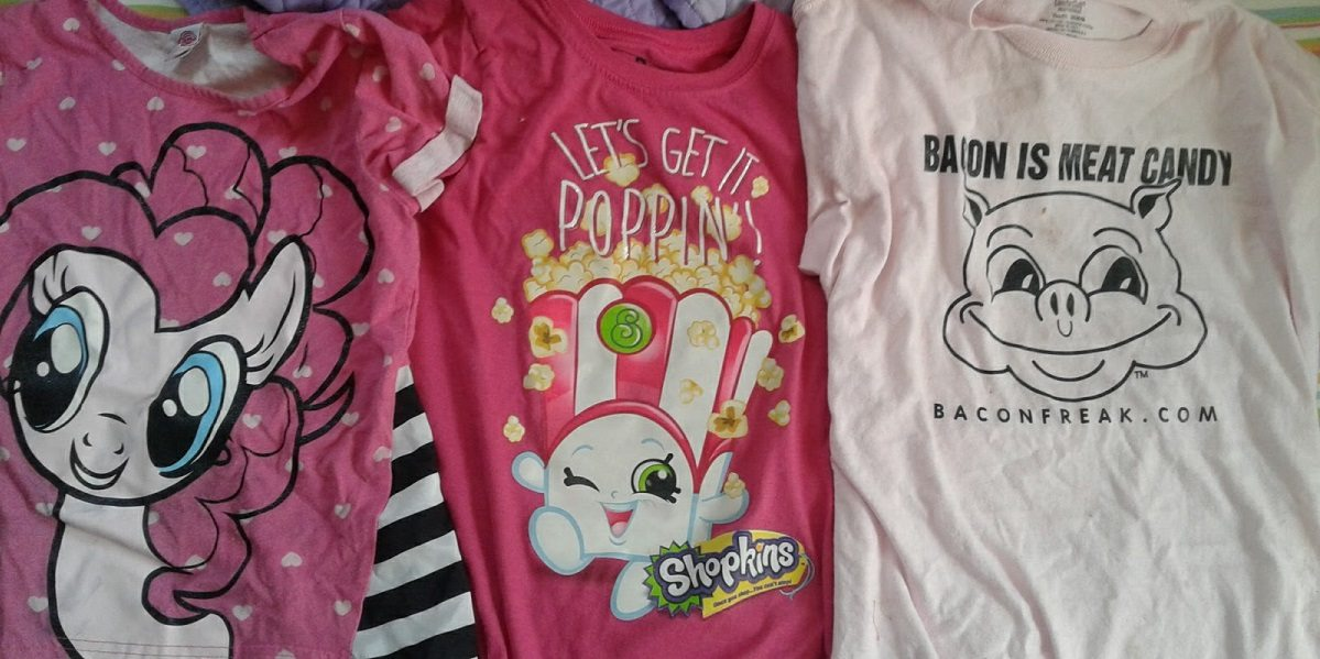 """Three t-shirts. One is the face of Pinky Pie. One is of the Shopkin """"Poppy Corn."""" The last has a pig that says """"Bacon Is Meat Candy"""" and the website baconfreak.com. All three shirts are pink."""