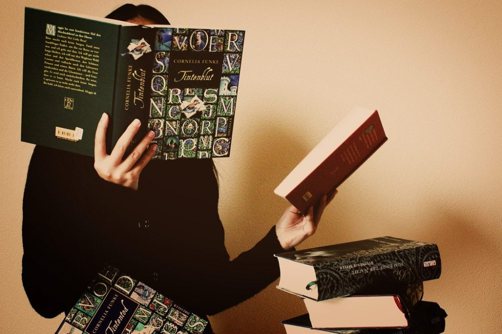 Person hidden behind a book with a large pile more to read.