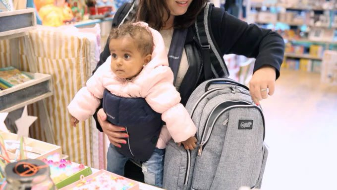 A woman with a baby strapped to her front reaches into a backpack on her side