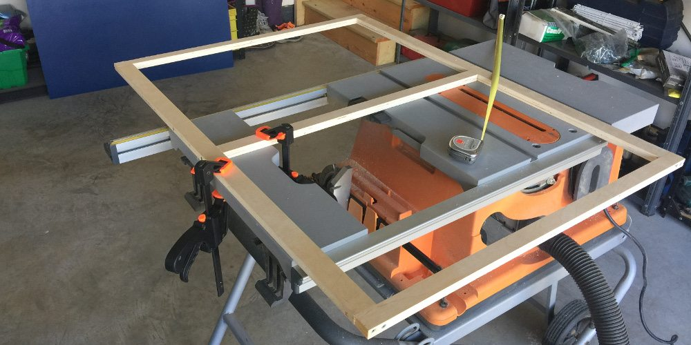 A wood frame clamped to a table saw.