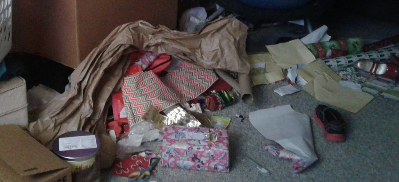 Floor cluttered with boxes, wrapping paper and supplies, packing material, and more