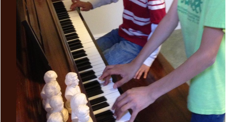 image of two children playing piano, a sight sure to bring a smile