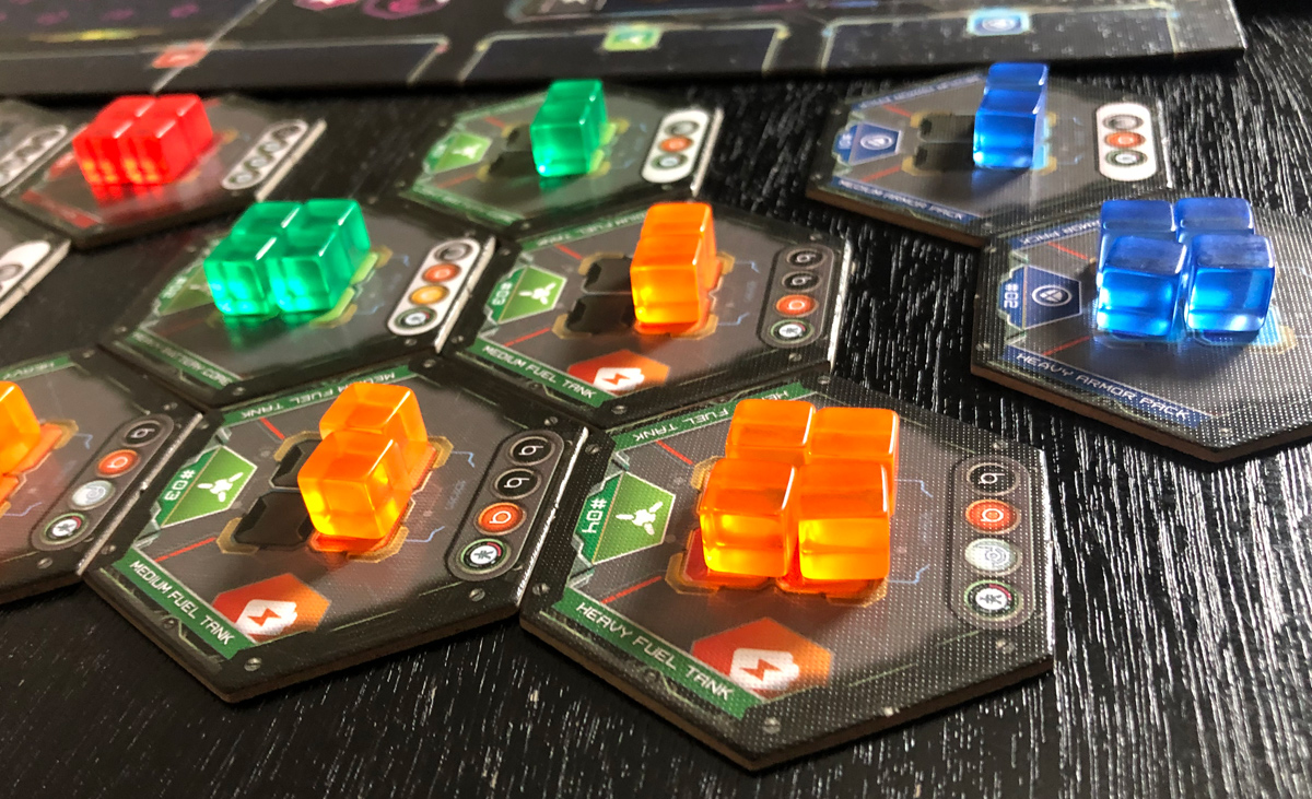 Close-up of game components including upgrade tiles and red, green, orange, and blue cubes. The lighting purposefully gives the cubes a glowing effect,