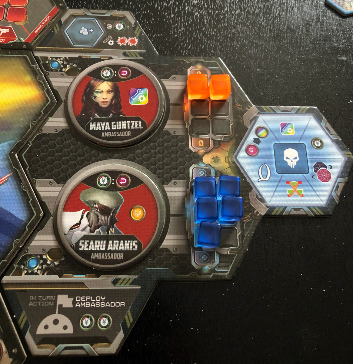 Overhead close-up photo of the mech combat panel showing placement of ambassadors and cubes.