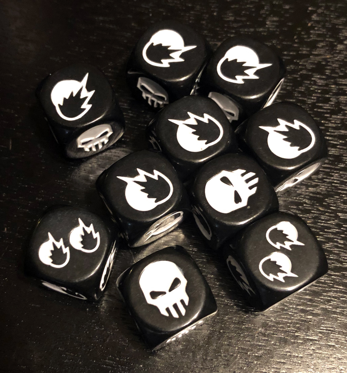 Close-up image of 10 black combat dice. The die faces feature a skull, one explosion, or two explosions in white.