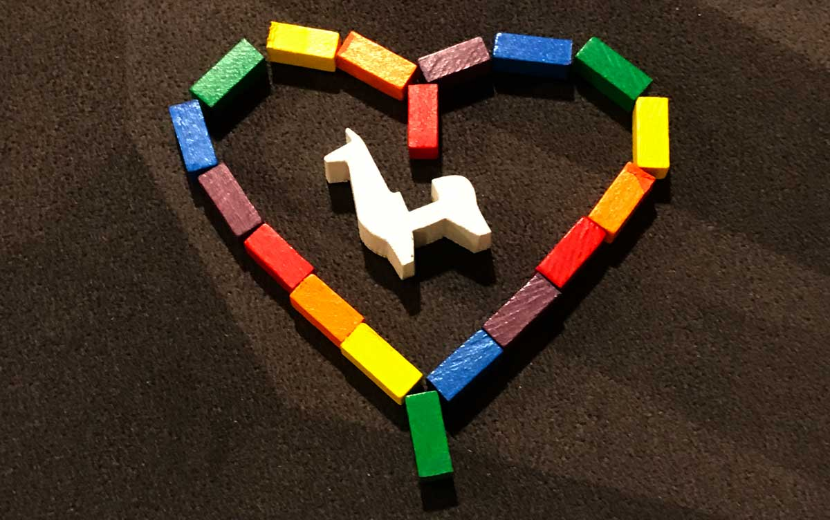 P'achakuna wooden pieces arranged in a heart, with llama meeple in the center
